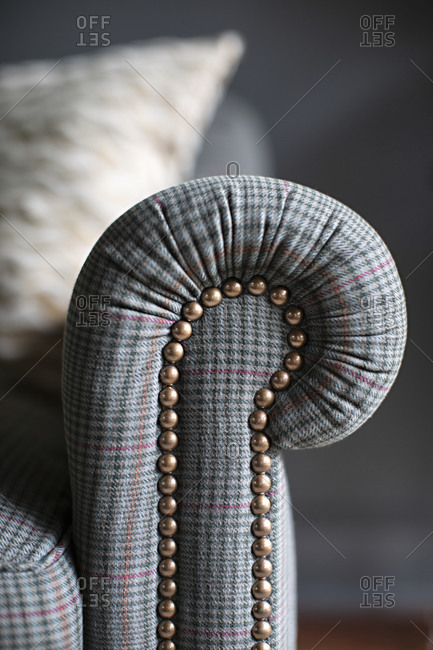 Detail of the arm of a gray plaid sofa with rivets