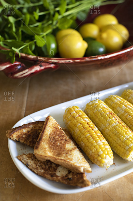 Toast and corn on the cob on wooden table by bowl of citrus fruit