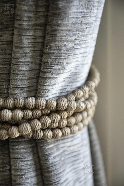 Natural beaded curtain tie-back around gray drapes