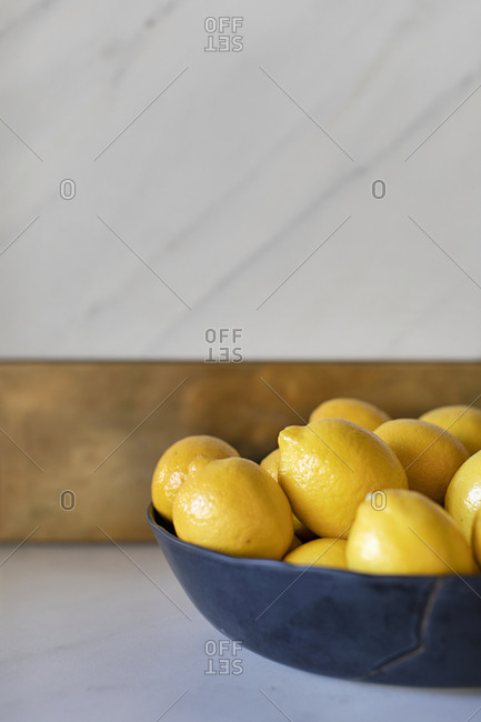 Black bowl filled with lemons on white marble counter