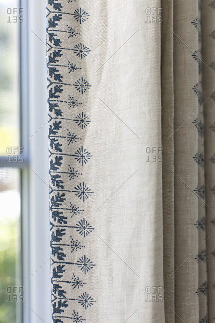 Blue and off-white drapes hanging in front of a window