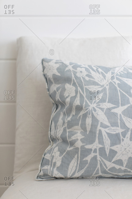 Gray and white throw pillow on a white sofa