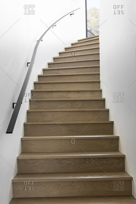 Winding wooden staircase with bright white walls