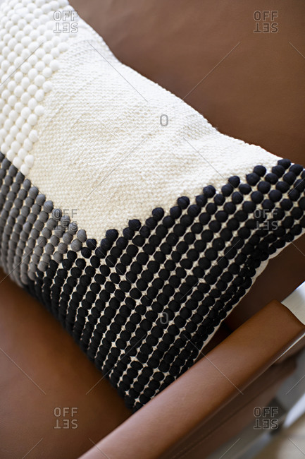 White throw pillow with black and gray dots on a brown leather seat