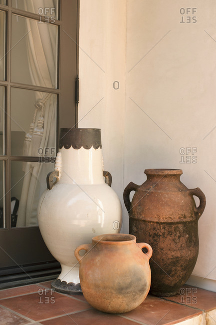 Three large decorative vessels on porch