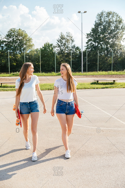 Portrait of two happy teenage Generation Z girls walking side by side at city park