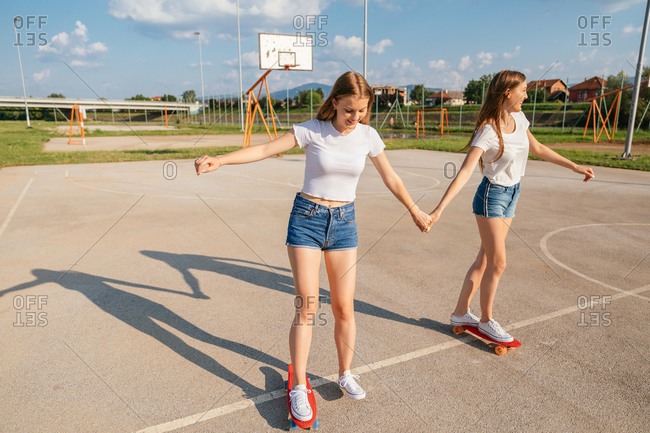 Two teenage Generation Z girls on skateboards