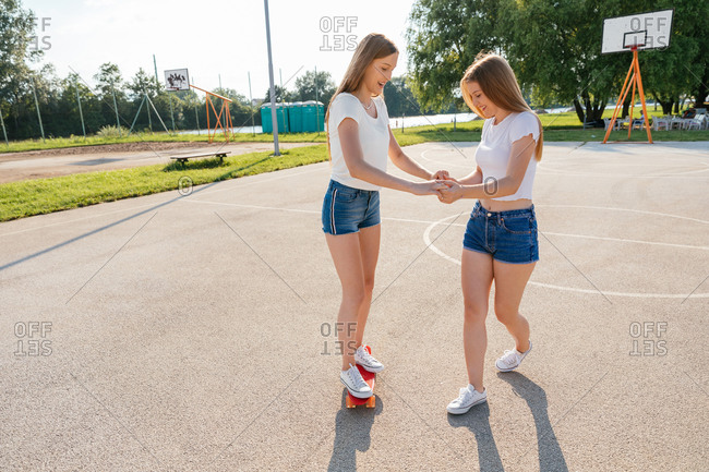Teenage Generation Z girls riding skateboards and holding hands while one helps the other balance
