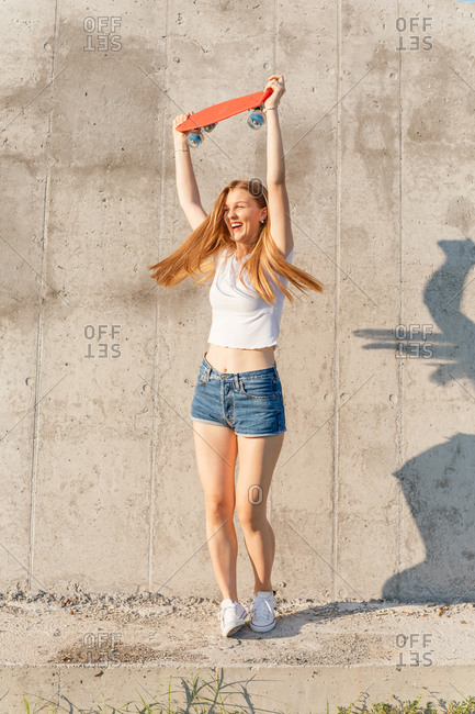 Portrait of a teenage Generation Z girl holding a skateboard up in the air