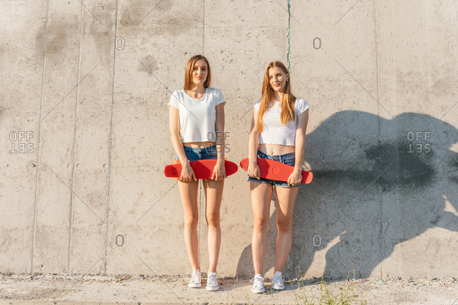 Two teenage Generation Z girls holding skateboards in front of concrete wall