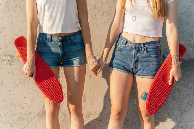 Teenage Generation Z girls holding skateboards and hands