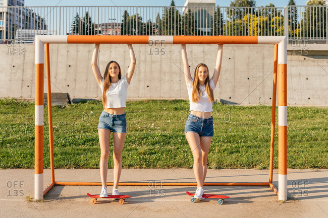 Two teenage Generation Z girls riding skateboards by sports goal