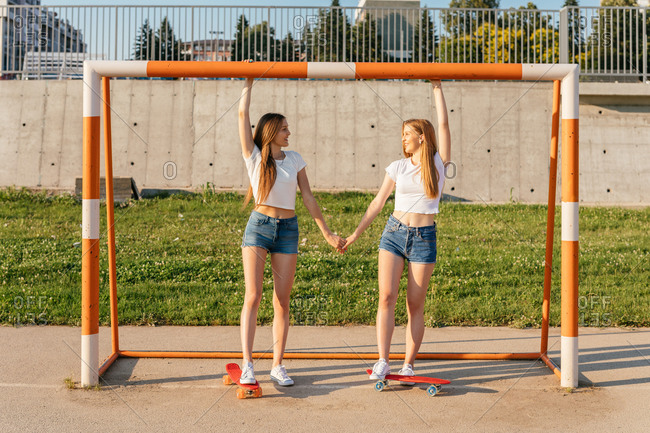 Two Generation Z girls riding skateboards by sports goal and holding hands