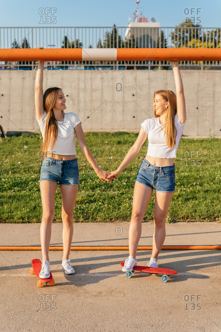 Happy Generation Z girls riding skateboards by sports goal and holding hands