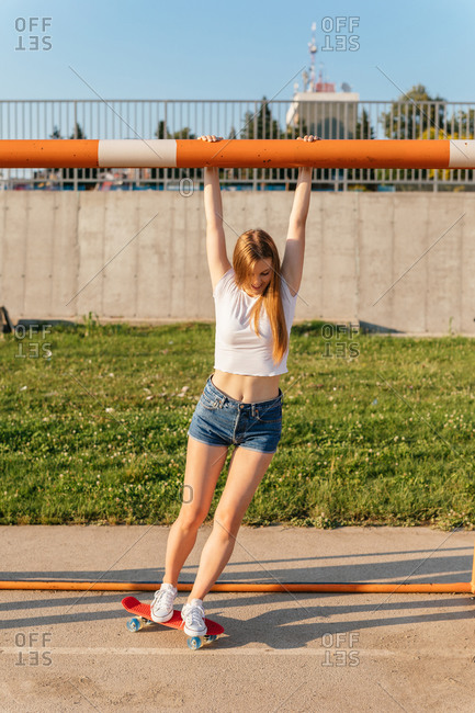 Teenage Generation Z girl riding a skateboard while hanging onto bar of a sports goal