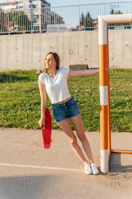 A teenage Generation Z girl holding a skateboard while hanging onto bar of a sports goal