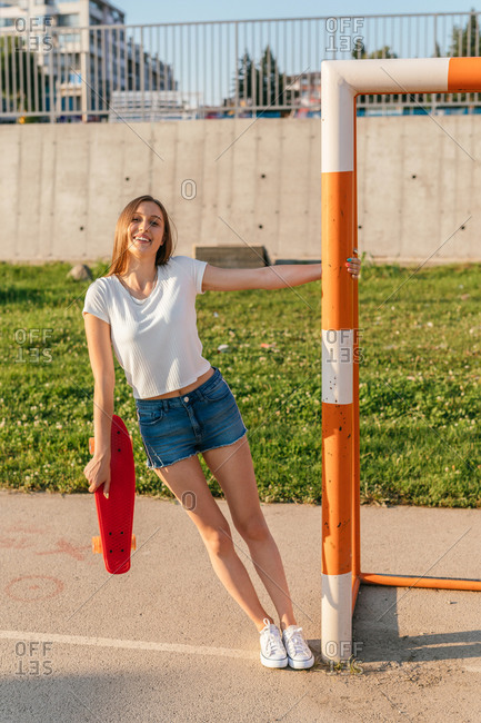 Happy teenage Generation Z girl holding a skateboard while hanging onto bar of a sports goal