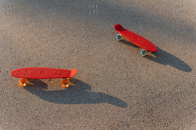 Two small red skateboards on ground at park