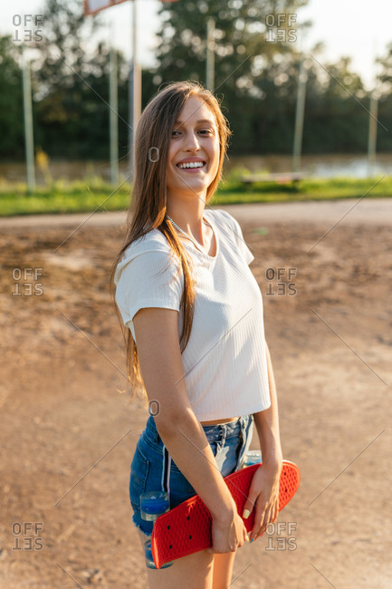 Portrait of a smiling teenage Generation Z girl holding a skateboard