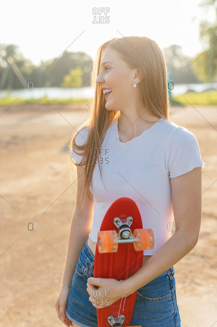 Portrait of a teenage Generation Z girl holding a skateboard during sunset at a park