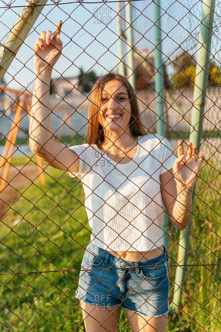Portrait of a happy teenage Generation Z girl standing behind fence
