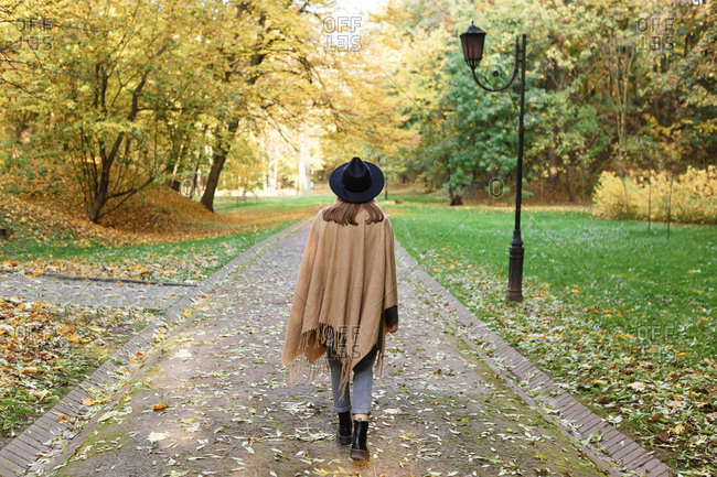 A young woman in a black hat and poncho is walking in the park in the autumn season