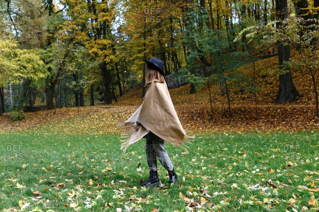 A young woman in a black hat and poncho is dancing on the colorful grass in the park in the autumn season