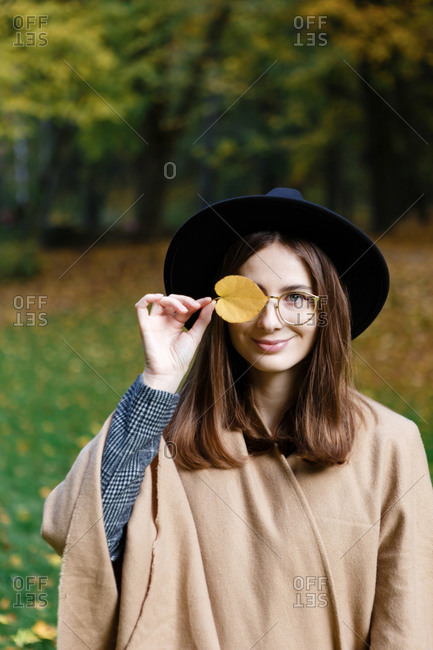 A portrait of the young woman in a black hat and poncho that is holding a yellow leaf in front of her face in the park in the autumn season