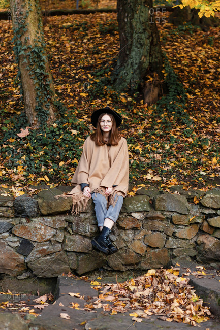 A young woman in a black hat and poncho is sitting on the small stone fence in the park in the autumn season