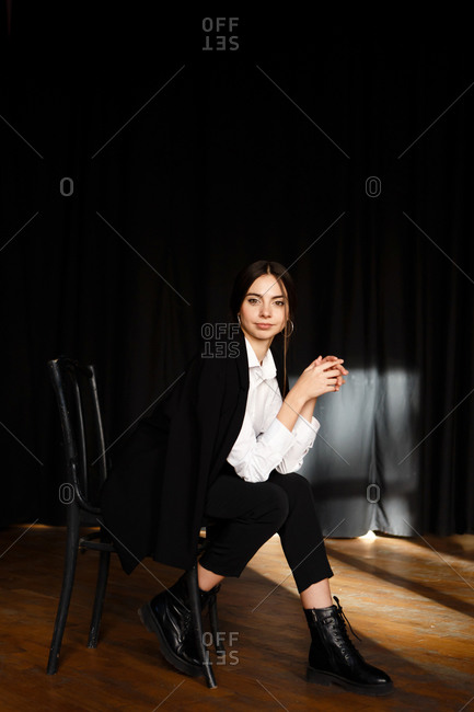 A portrait of an actress woman in formal suit who is sitting on the chair at the stage