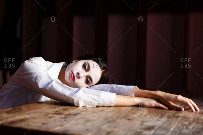 A portrait of an actress woman in a shirt who is sitting on the chair and posing on the table with theatrical makeup