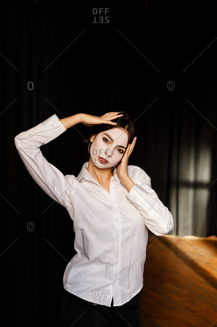 A portrait of an actress woman in a shirt and with done theatrical makeup who is posing like a mime
