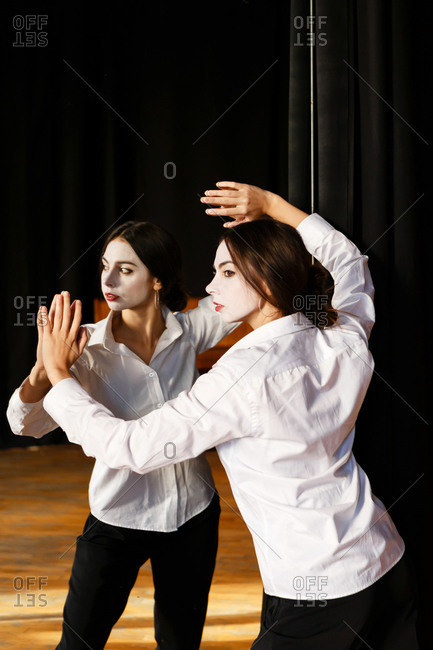 A portrait of an actress woman in a shirt and with done theatrical makeup who is posing like a mime and looking at her reflection