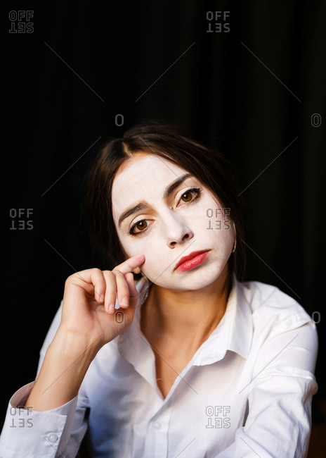 A portrait of an actress woman in a shirt and with done theatrical makeup who is posing like a mime by demonstrating different emotions