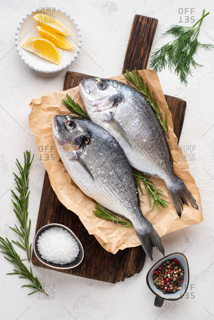 Fresh uncooked dorado fish on dark wooden chopping board over white background, top view