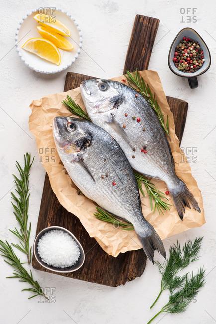 Fresh uncooked dorado fish on dark wooden chopping board over white background, overhead