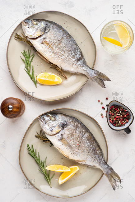 Top view of cooked dorado fish served on plate with lemons and herbs