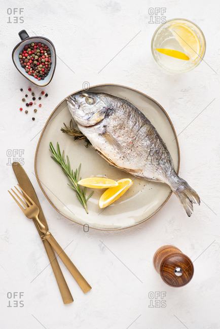 Overhead view of cooked dorado fish served on plate with lemons, herbs, and peppercorn
