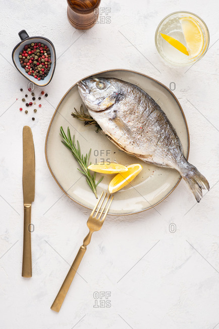Overhead view of cooked dorado fish served on plate with lemons and herbs