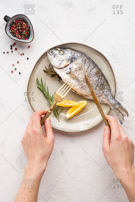 Overhead view of cooked dorado fish served on plate with lemons and herbs. Hands of anonymous person using fork and knife