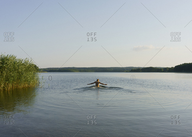 Boy swimming in sunny tranquil lake, Uckermark, Germany
