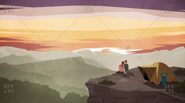 Couple enjoying majestic sunset mountain view outside tent