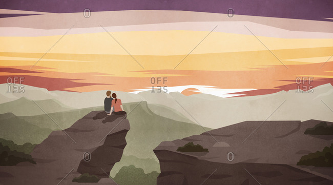Couple enjoying majestic scenic mountain landscape at sunset