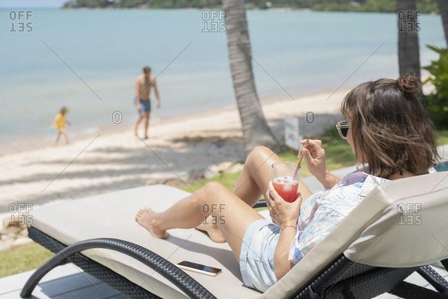 Woman enjoying cocktail on sunny beach lounge chair