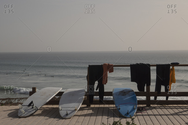 Surfboards and wetsuits drying on sunny beach boardwalk, Taghazout, Morocco