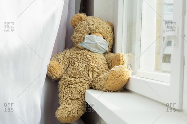 Teddy bear wearing face mask in windowsill