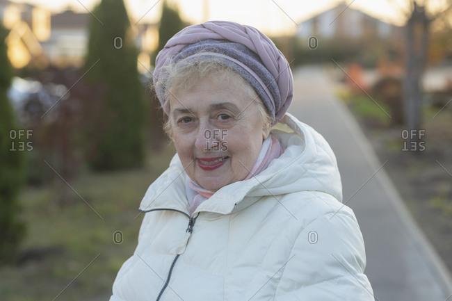 Portrait happy beautiful senior woman in winter coat on sidewalk