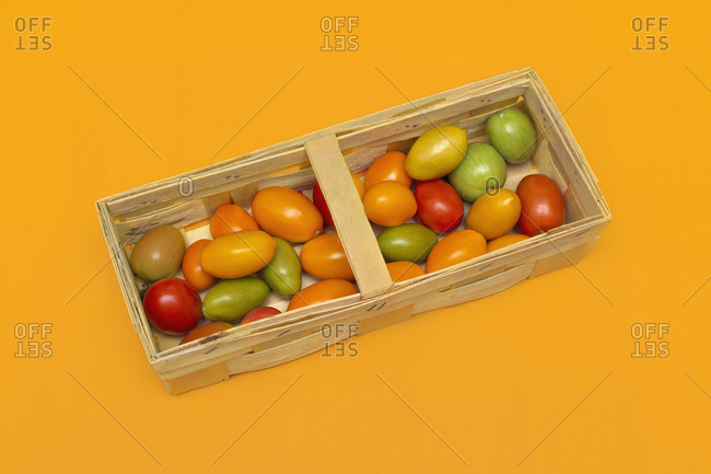 Fresh multicolor cherry tomatoes in crate on orange background