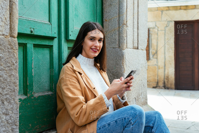 Young woman sitting and texting a message on smartphone outdoors