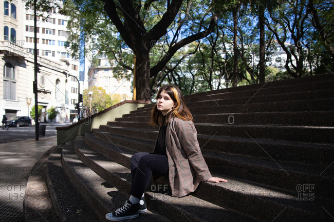 Girl sits on the steps of the city square in Buenos Aires